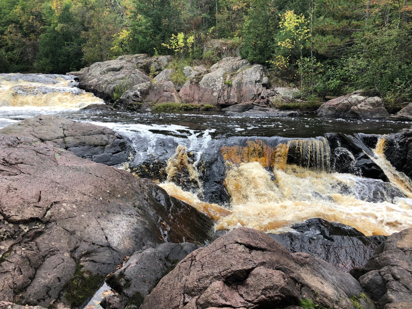 brown water cascades over large boulders in rapid river