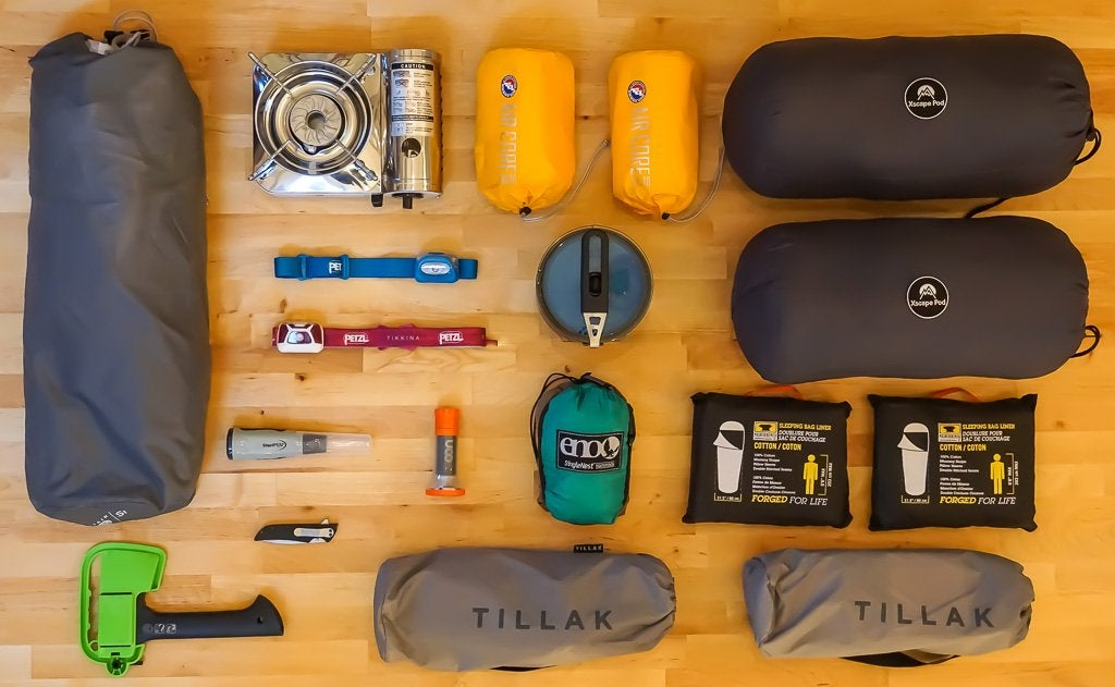 Gear arranged on wooden floor: tents and sleeping bags in stuff sacks, headlamps, a camp stove and cooking utensils are visible