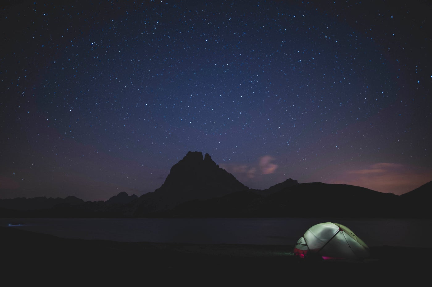 a tent with a light inside it on a silhouetted campsite under a purple and blue night sky
