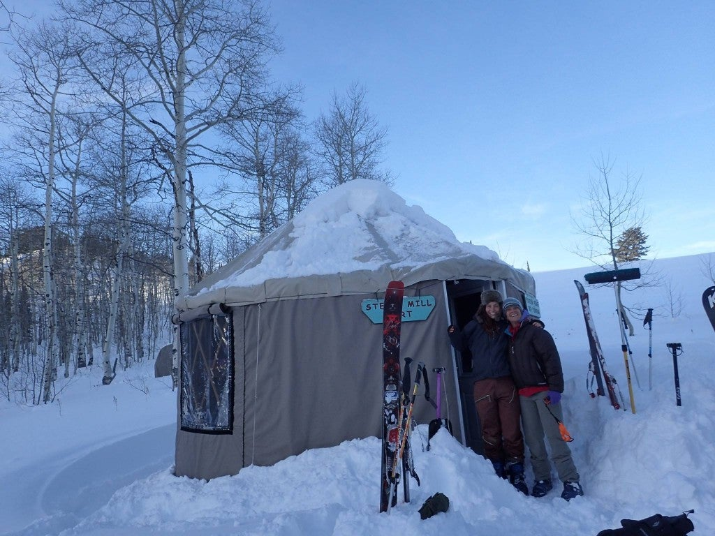 Two friends hugging in front of yurt with snow scene