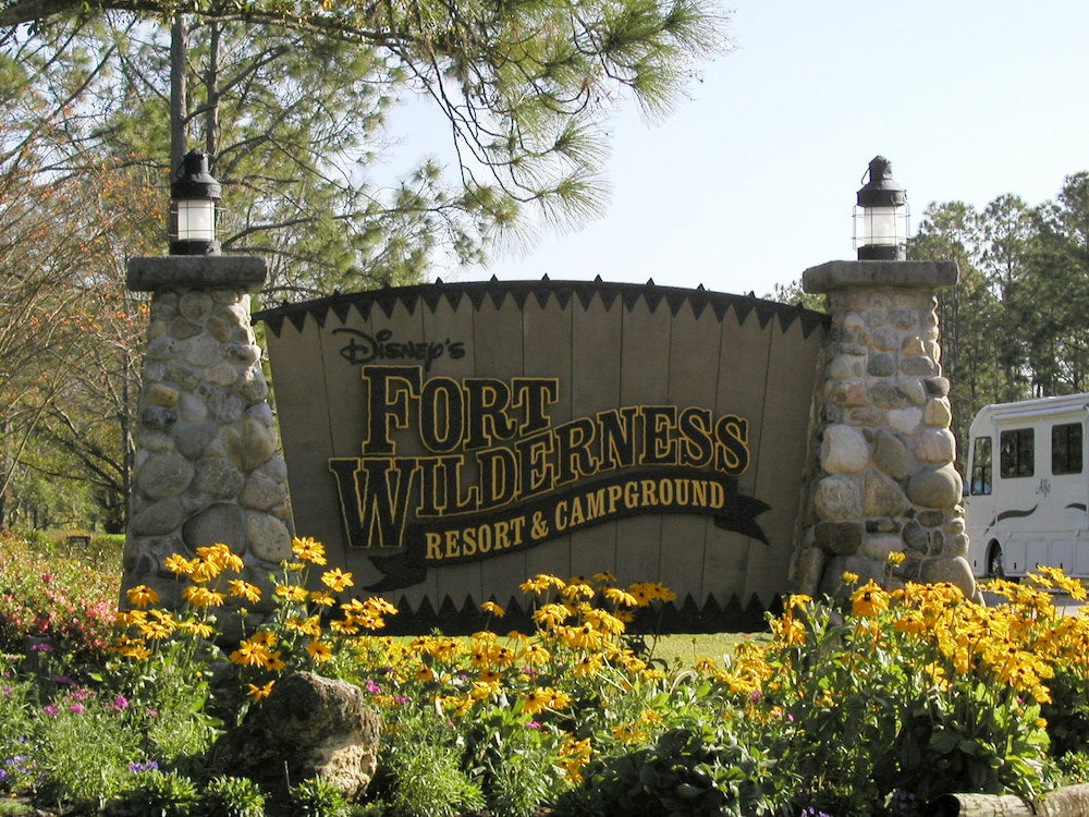 Fort Wilderness campground sign with yellow flowers in foreground