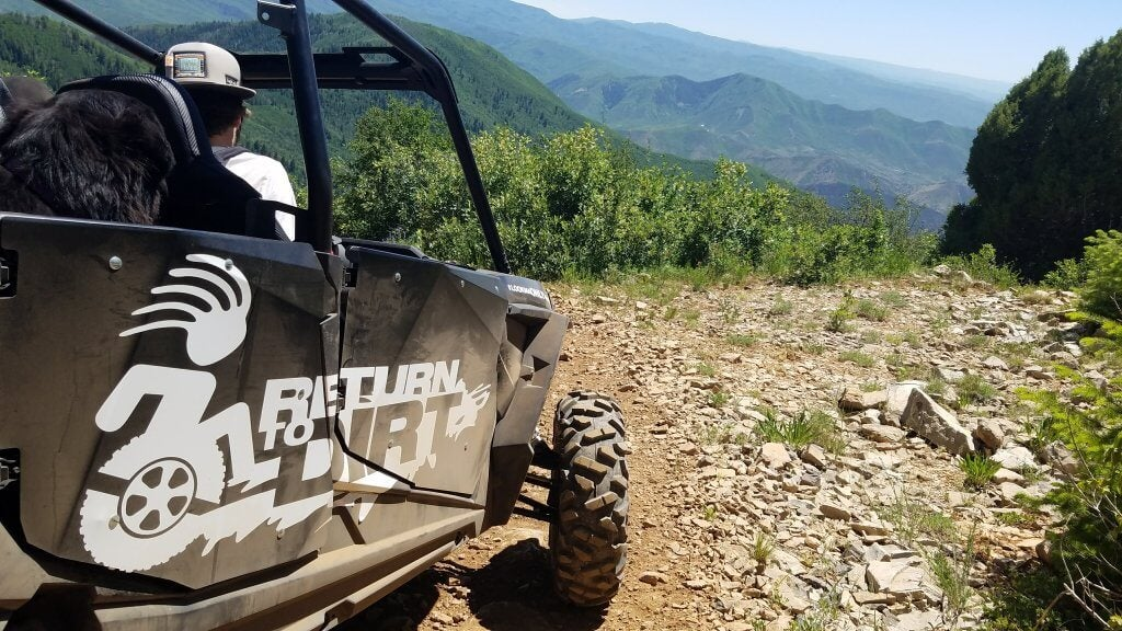 Return To Dirt ATV on rocky road with mountains in background
