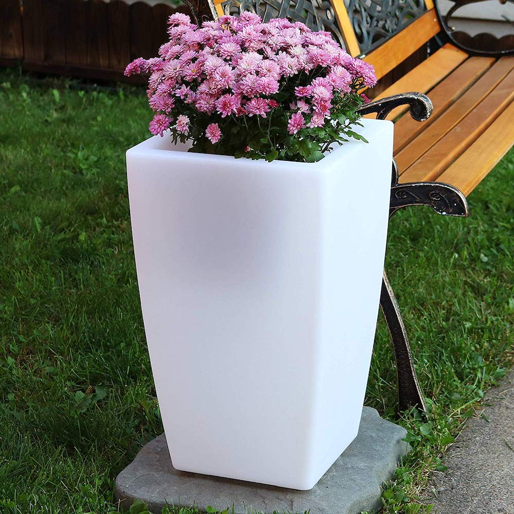 White planter with flowers in it and grass in background