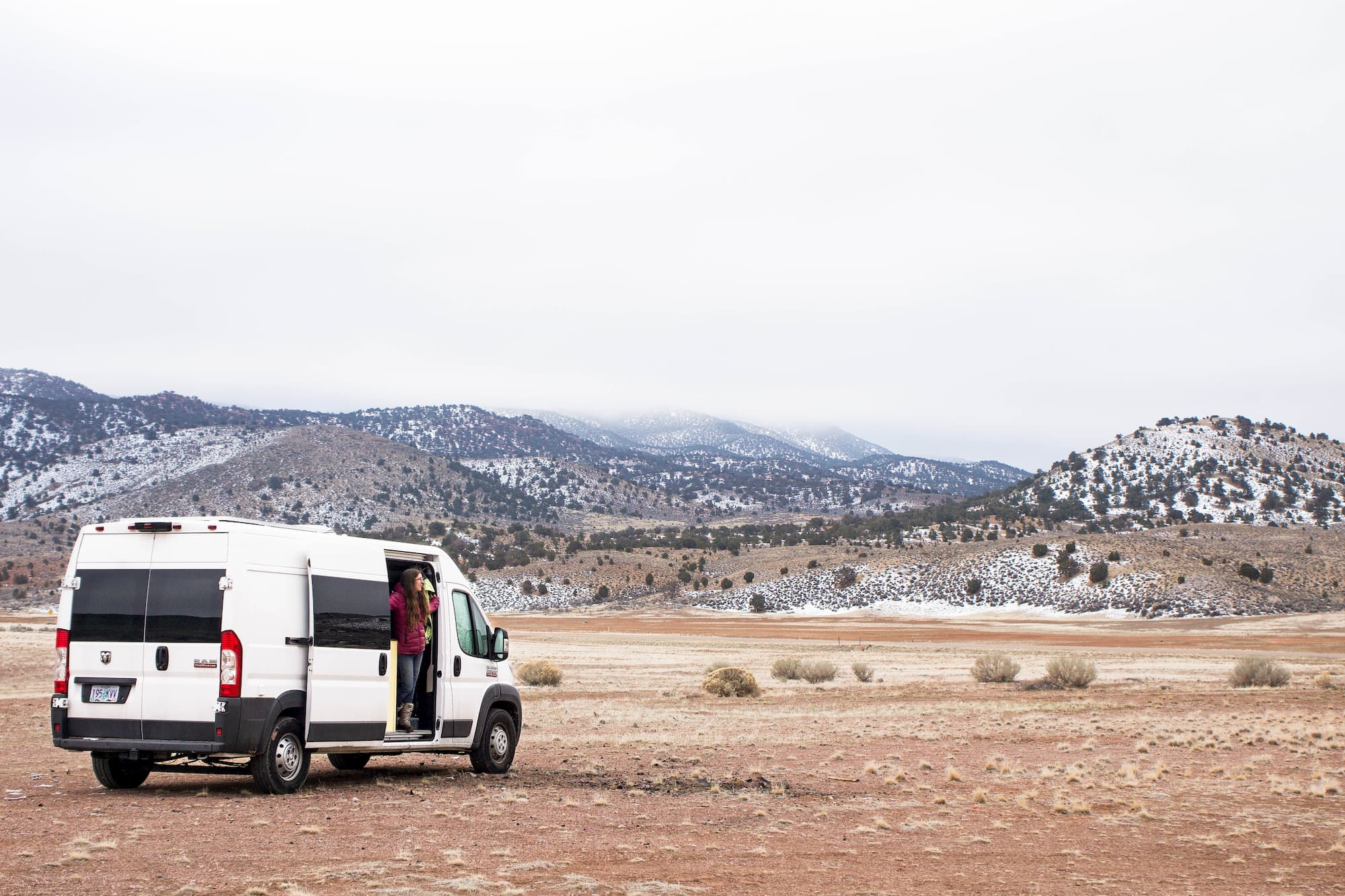 a woman stepping out of a van on a desert with snowy mountains in the background