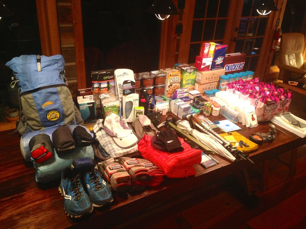 An array of gear and food laid out on table before a thru-hiking trip