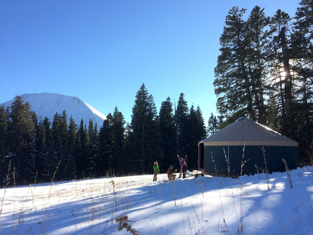 Yurt in snow covered field with large mountain in background