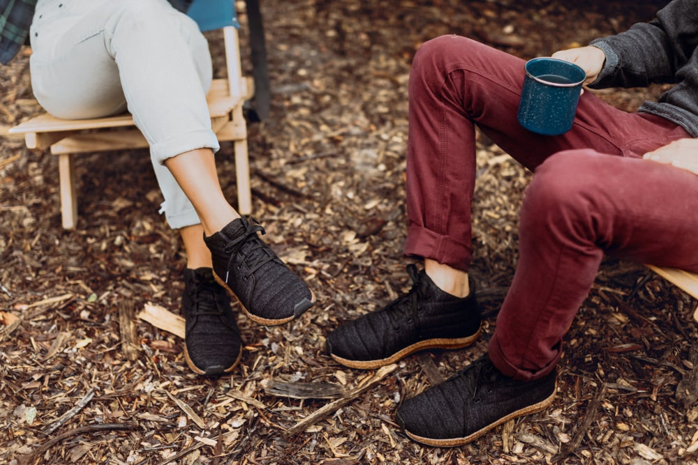 two people sitting in camping chairs and wearing eco-friendly shoes