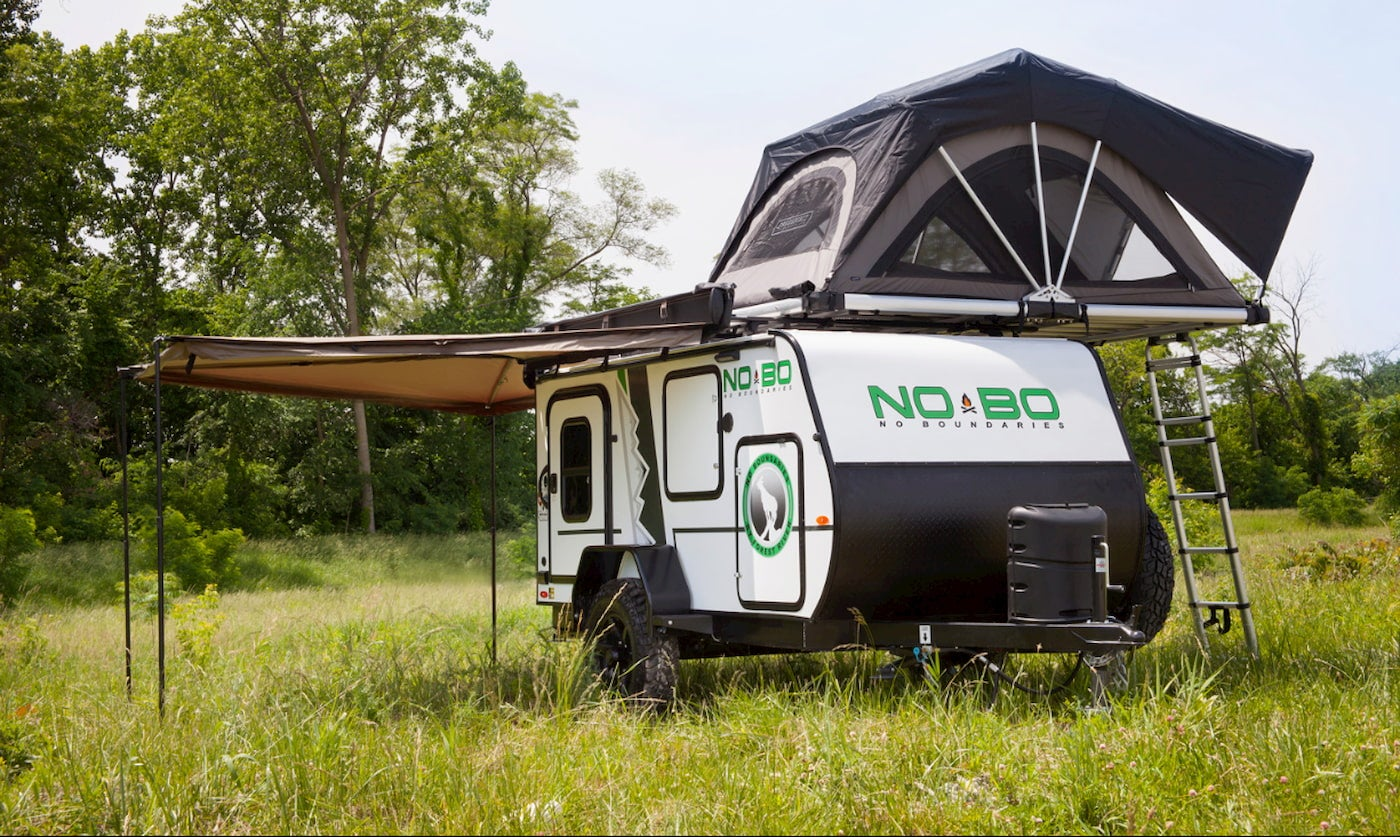 The nobo setup in a field with awning and rooftop tent