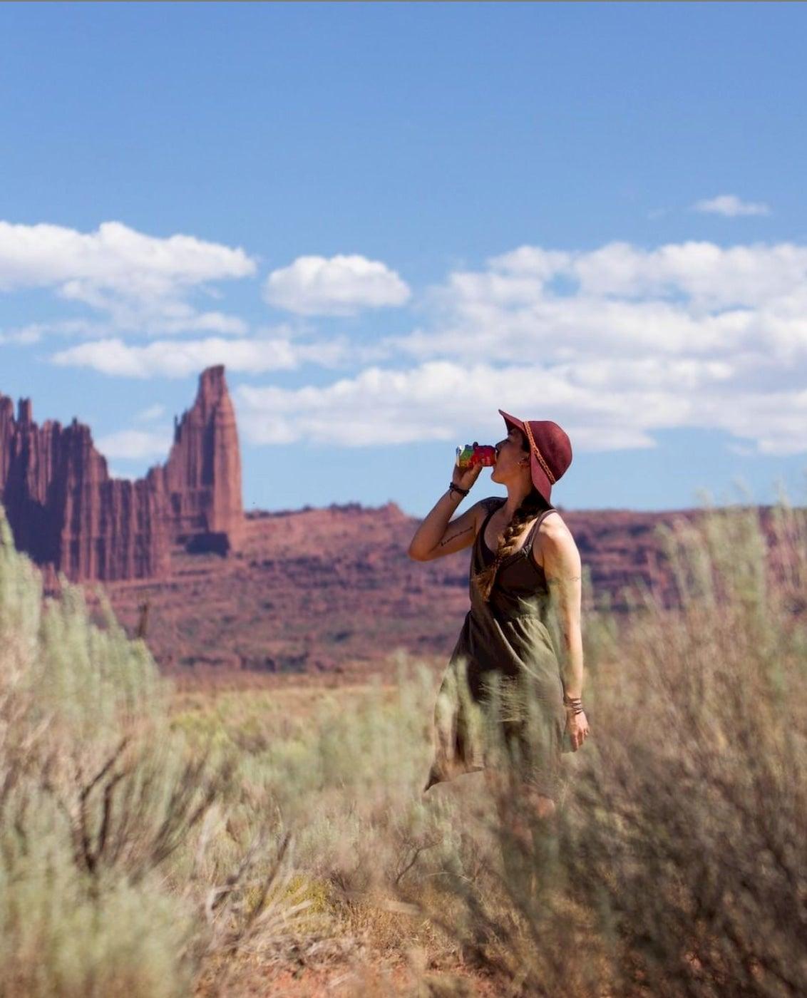 Megan drinking a soda in a field and felt hat in Utah.