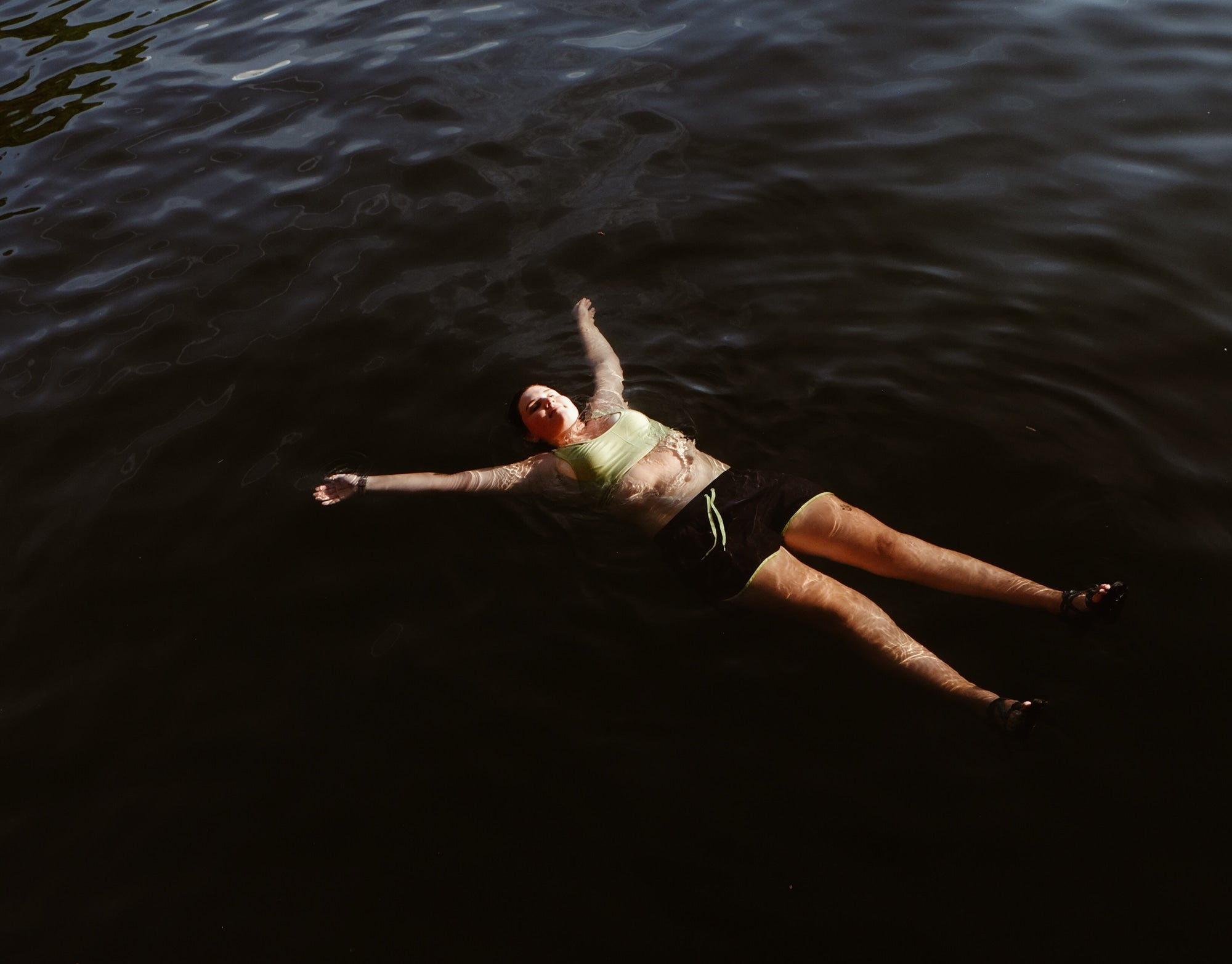 Woman floating in a lake in a sports bra and shorts