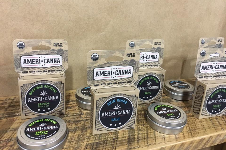 four americanna cbd balm packages on display in boxes and tins