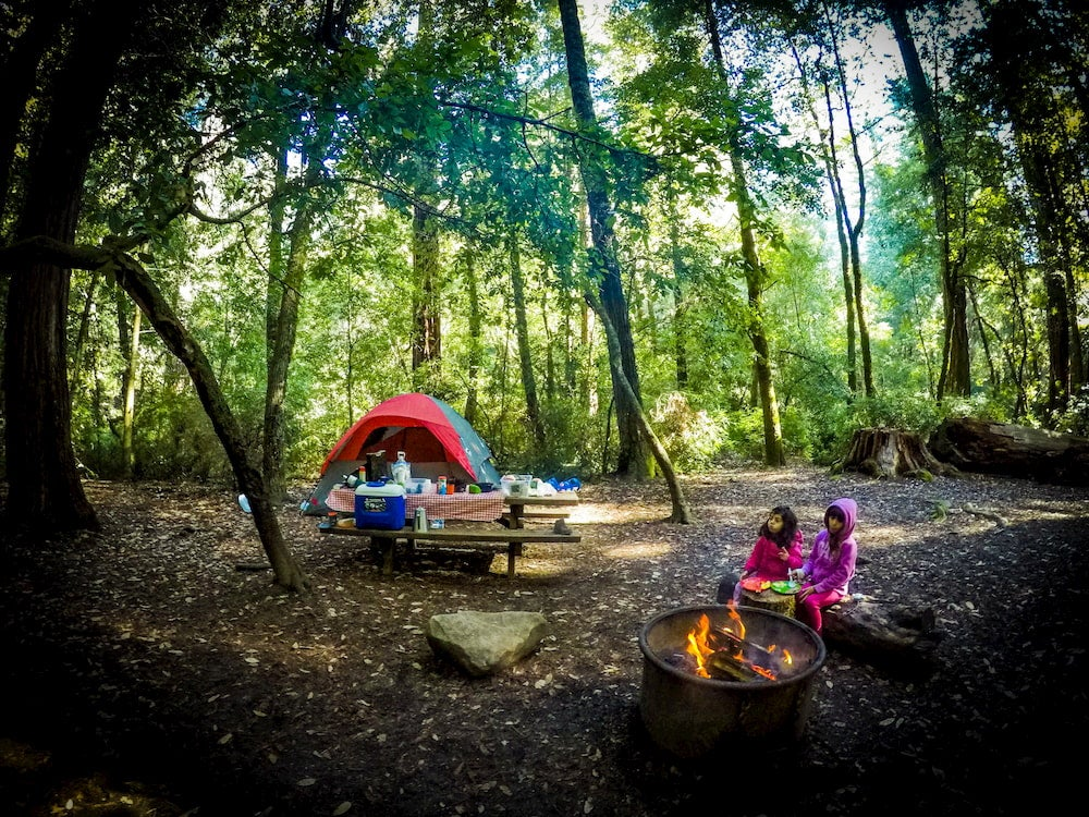 Campsite with two young girls sitting around campfire while camping in Santa Cruz county, California