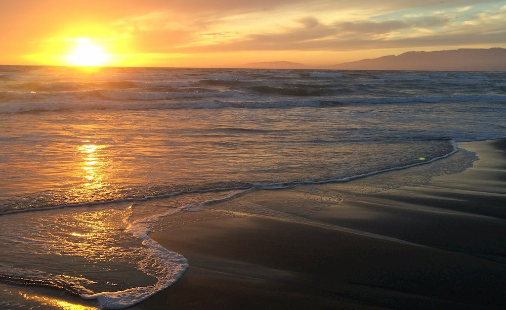 a panoramic shot of the pacific ocean from a california beach at sunset