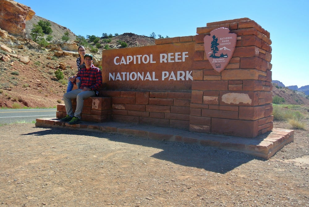 Two people sitting on captiol reef national park sign