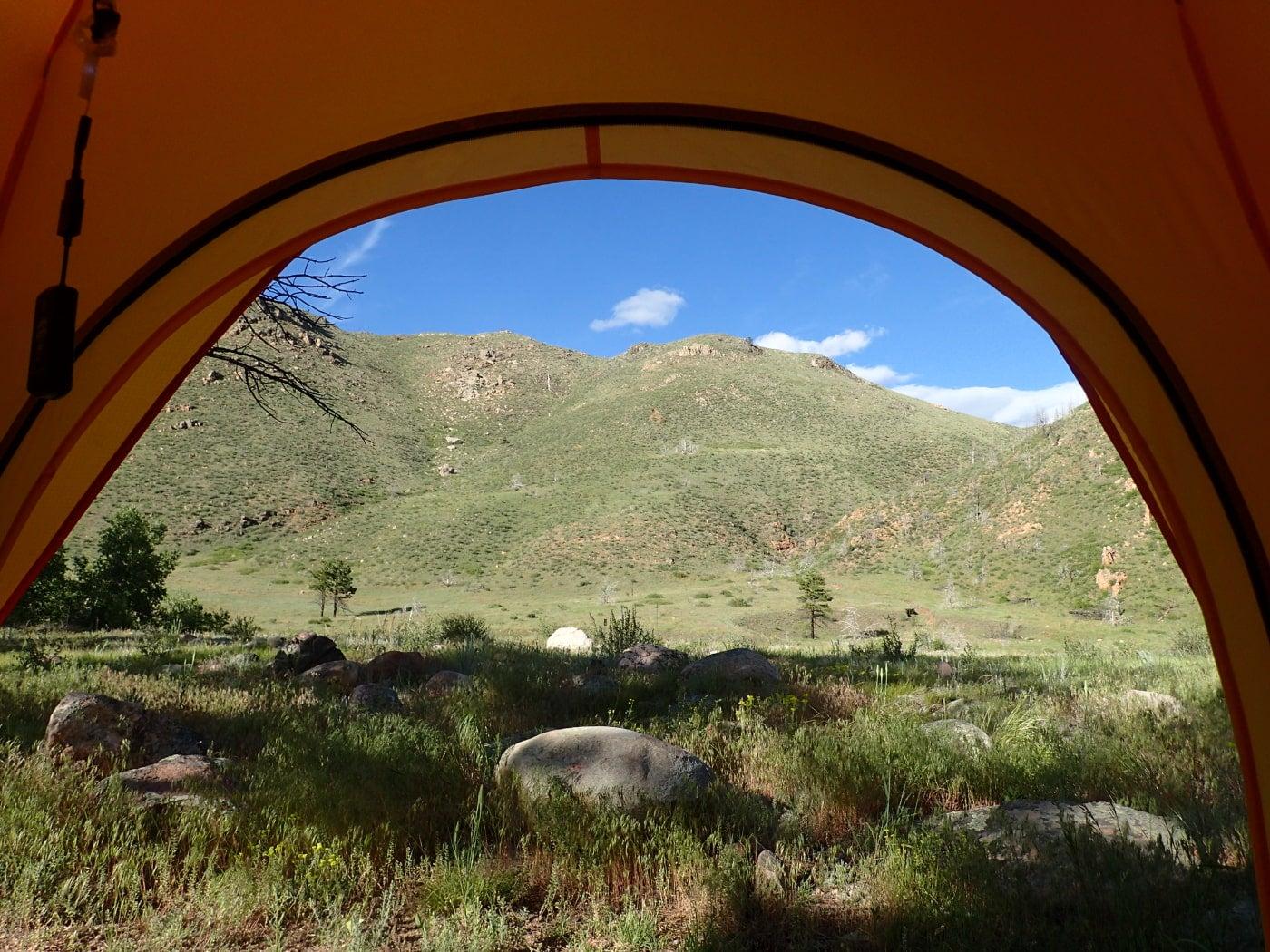 View of a colorado mountain through the door of an orange tent.