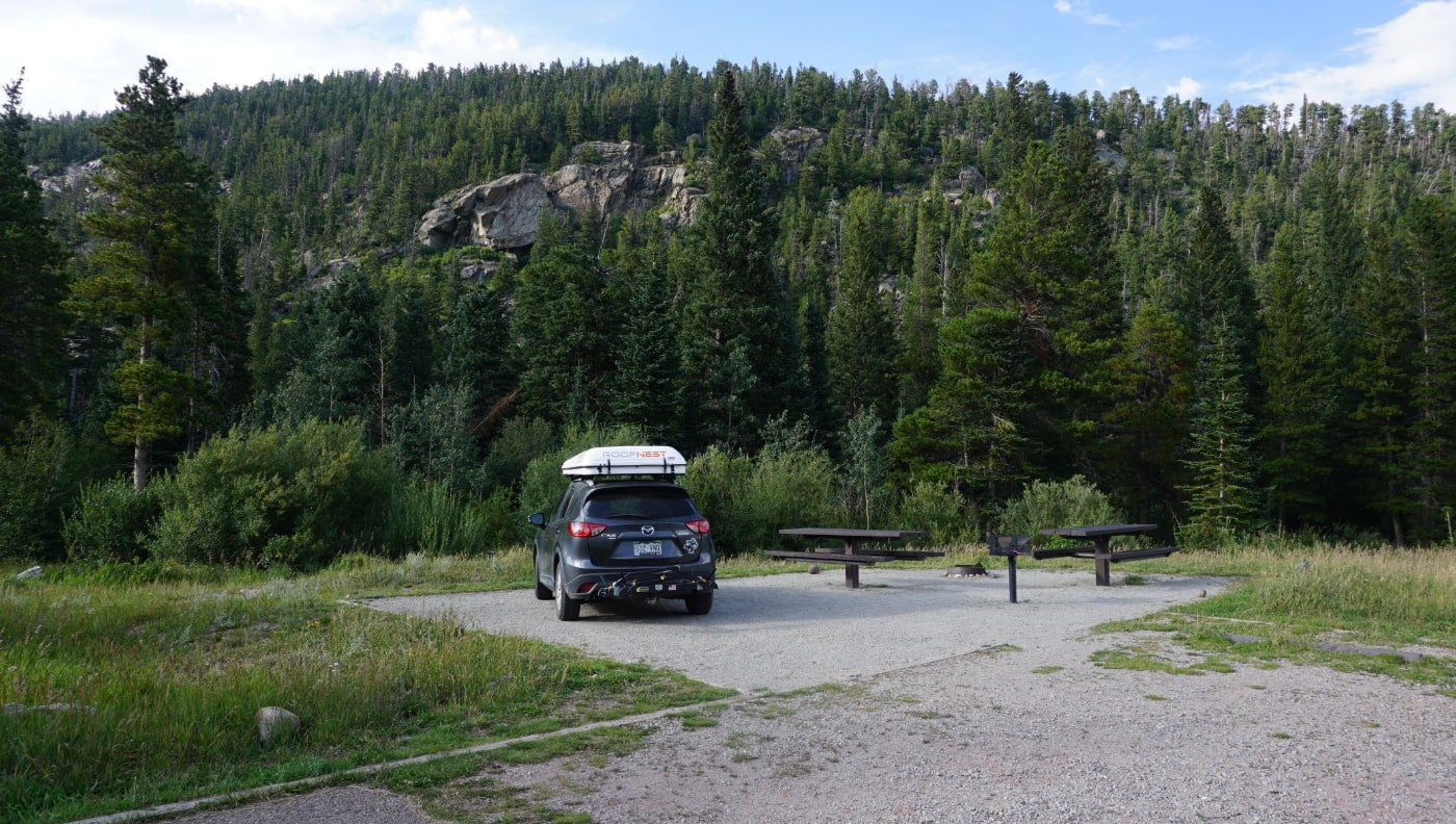 Black SUV with white roofbox parked in drive in campsite with picnic tables in Colorado.