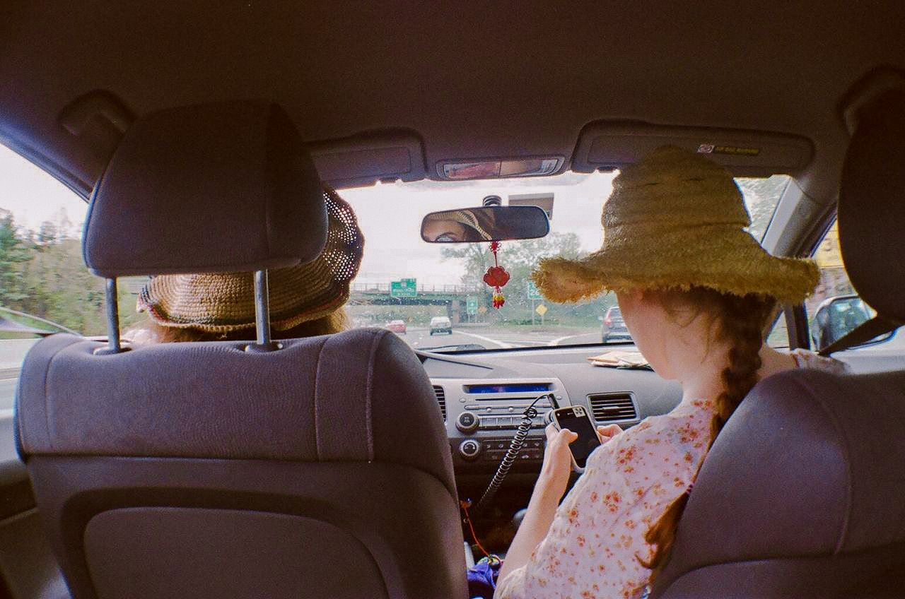 backseat view of two women in car as passenger searches for a road trip playlist on phone
