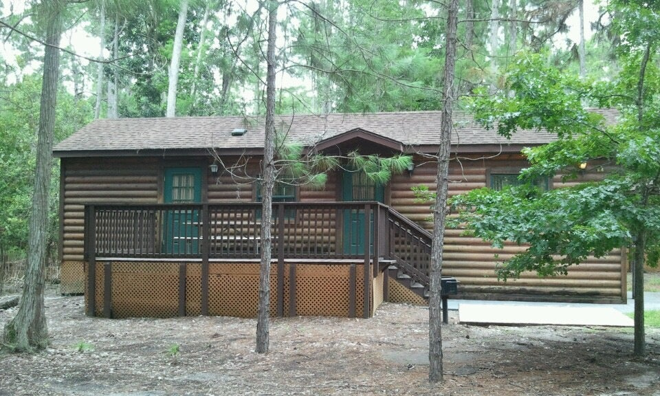 Brown and green cabin with trees in front of it