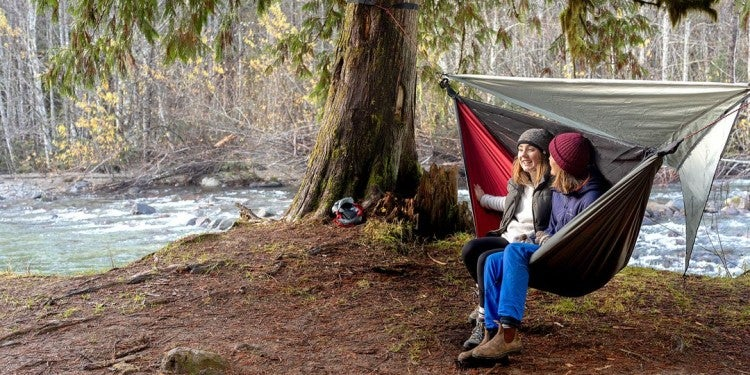 two women sit in a hanging 4-season hammock near a river in winter