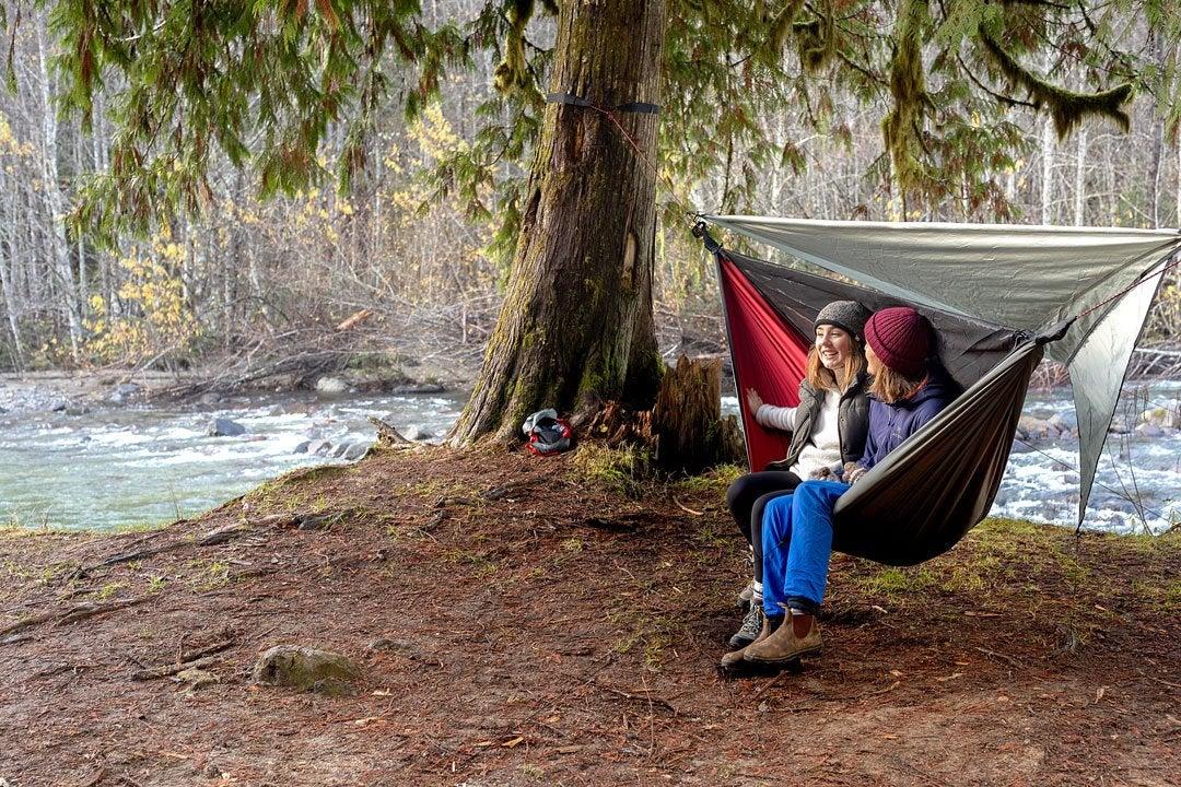 two women sit in a hanging 4-season hammock near a river in winter