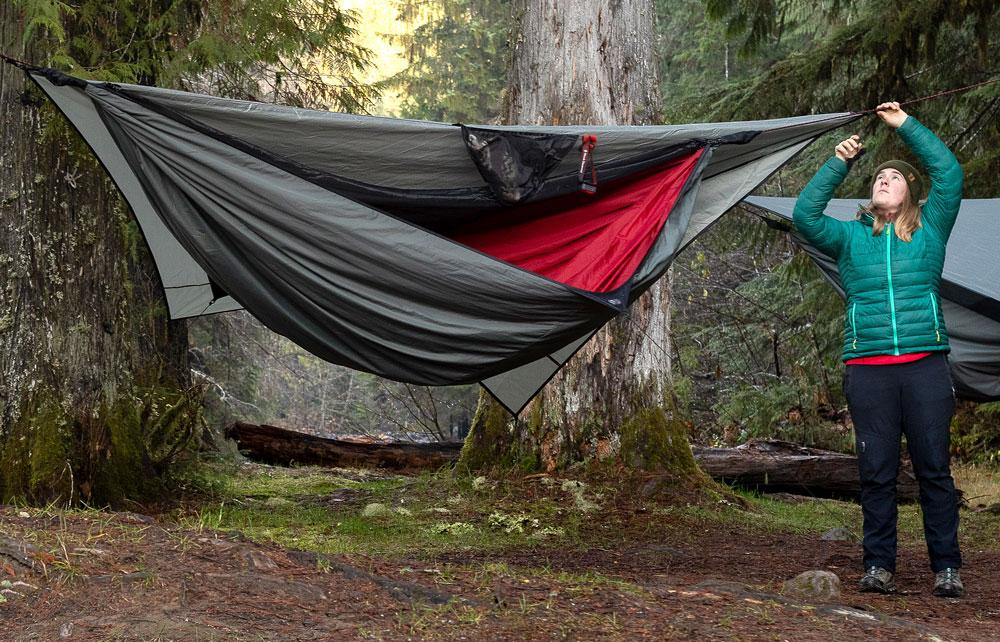 a woman in a blue jacket ties one side of a 4-season hammock to a tree