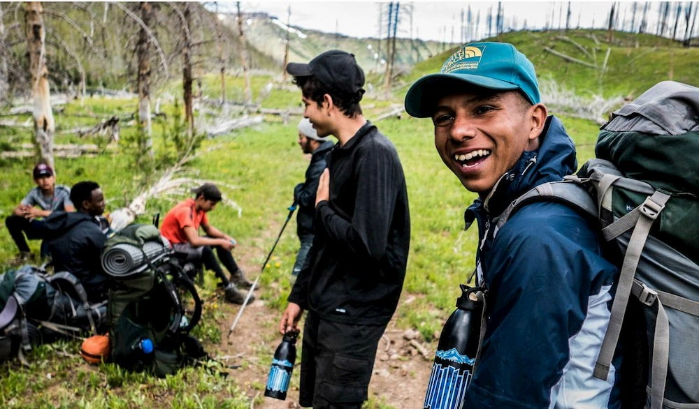 Laughing boy with several friends around him all backpacking in the mountains