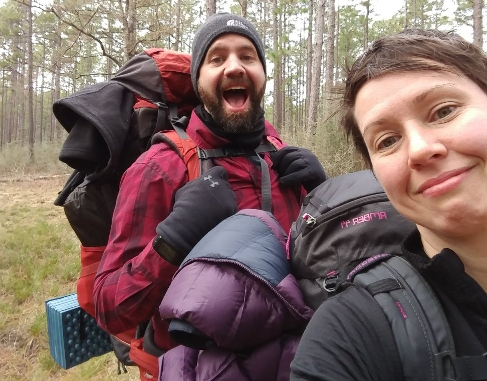 Two people smiling facing forward with backpacks on and forest in background