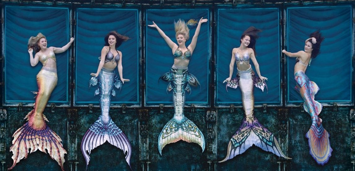 Aerial view of five Weeki Wachee Mermaids with colorful tails