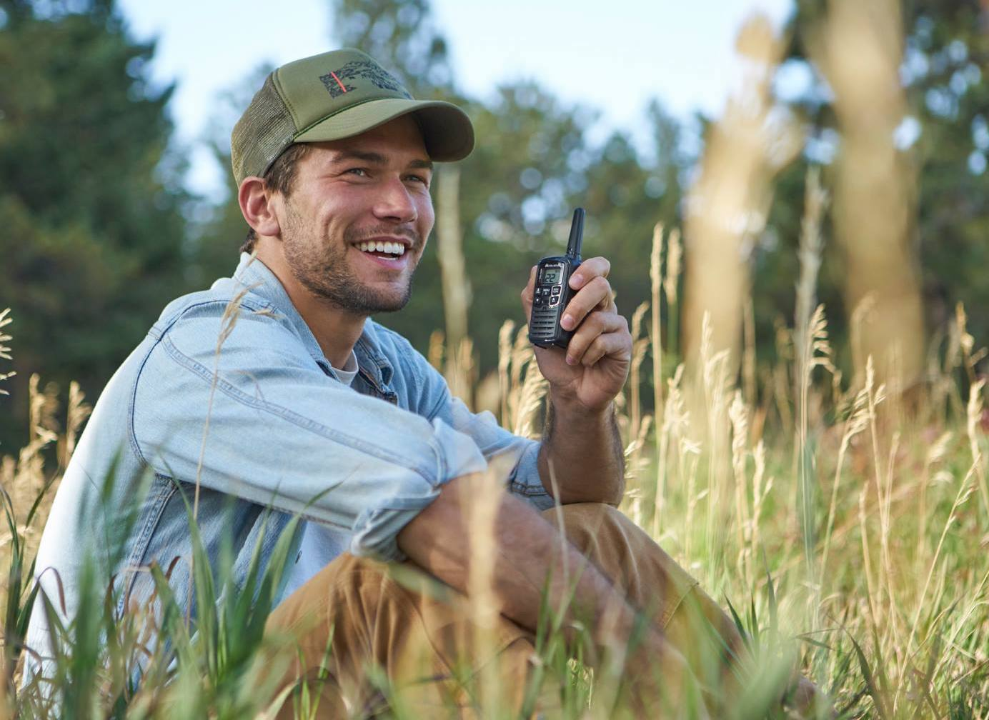 a man smiling in the woods holding a midland walkie talkie