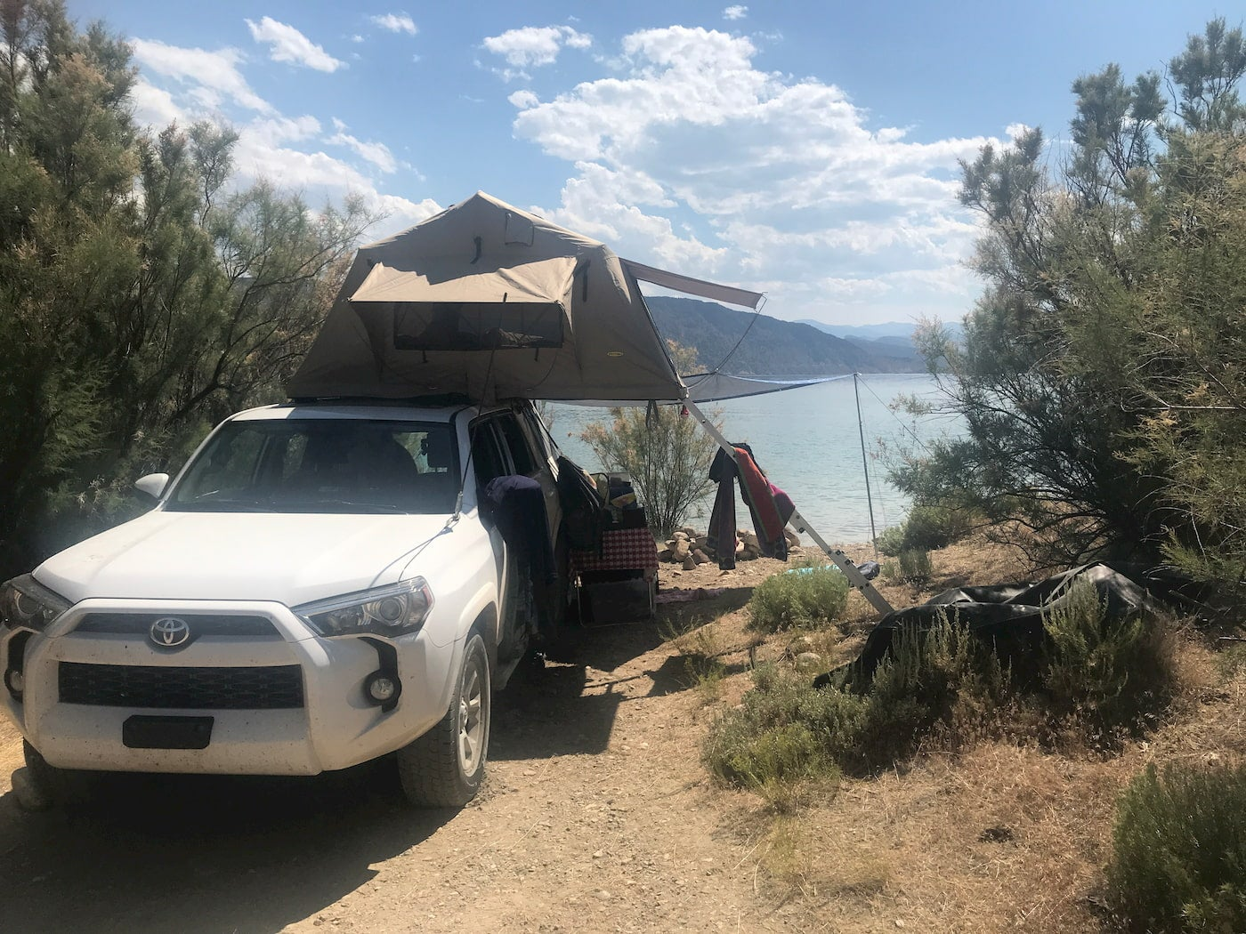 White truck with rooftop tent parked beside a lake at Navajo Cliffs Utah.