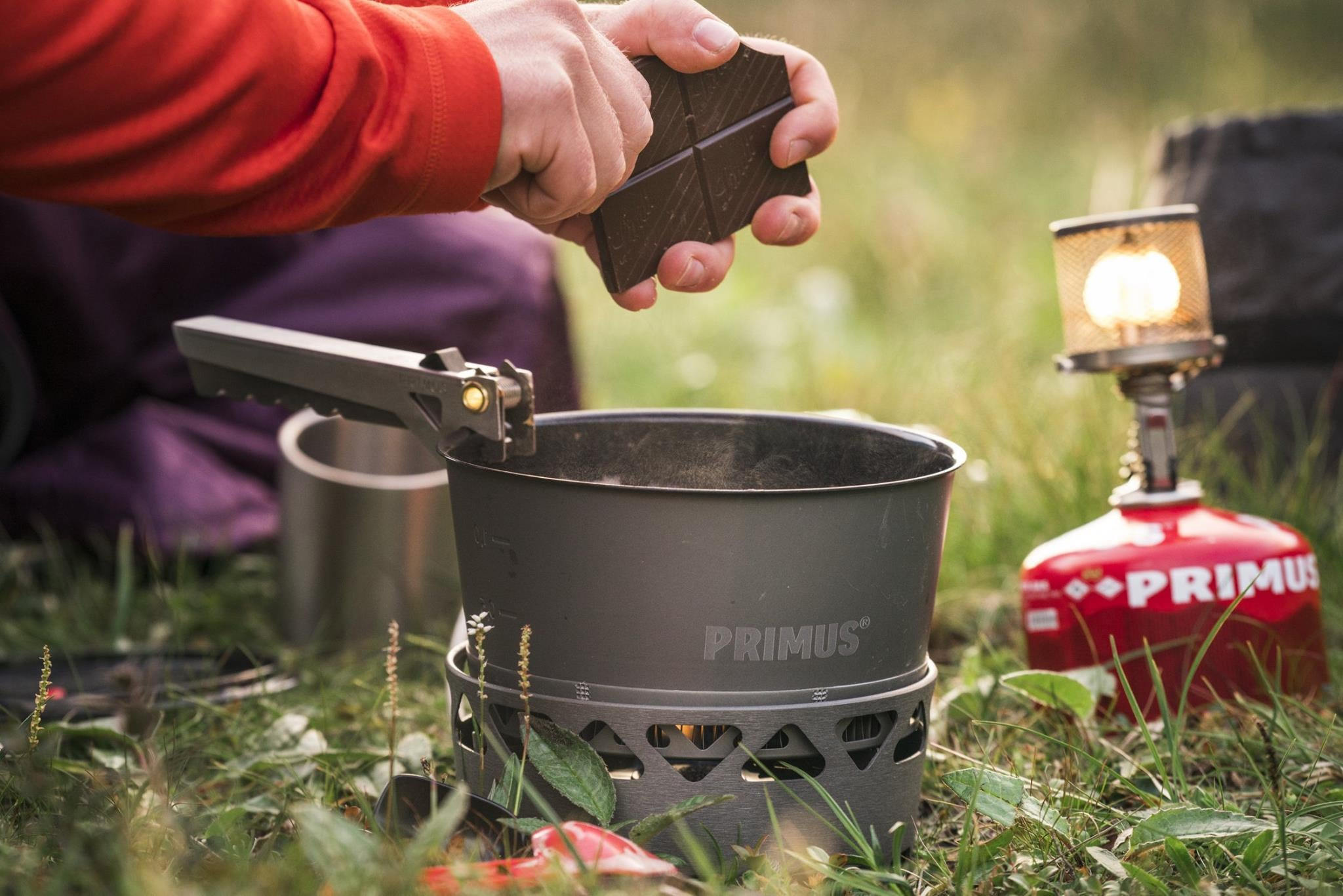 a hand dropping chocolate into a pot over a primus portable stove