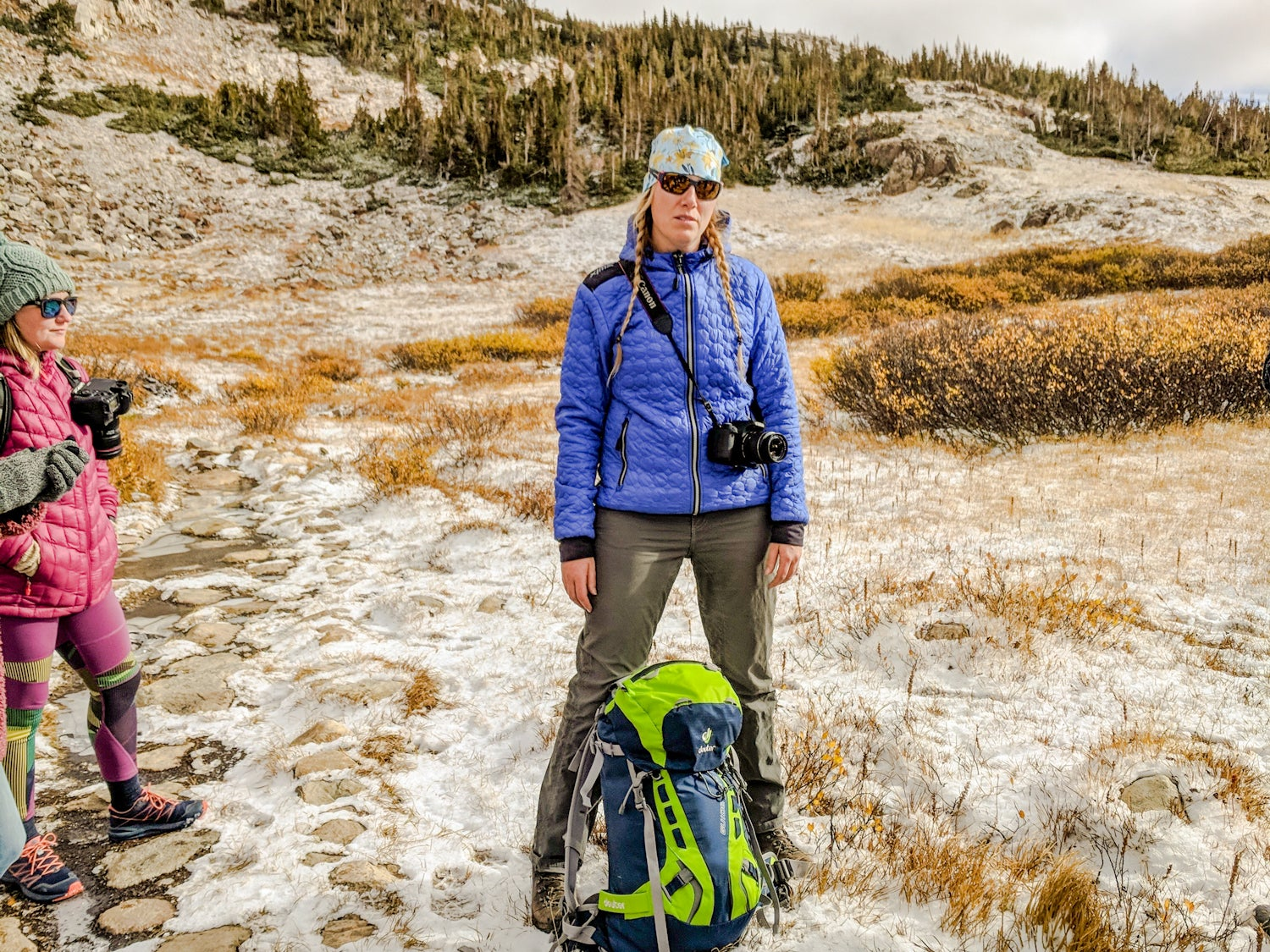 Rebecca Walsh stands with another woman hiker with a backpack in front of her in the backcountry of Wyoming.