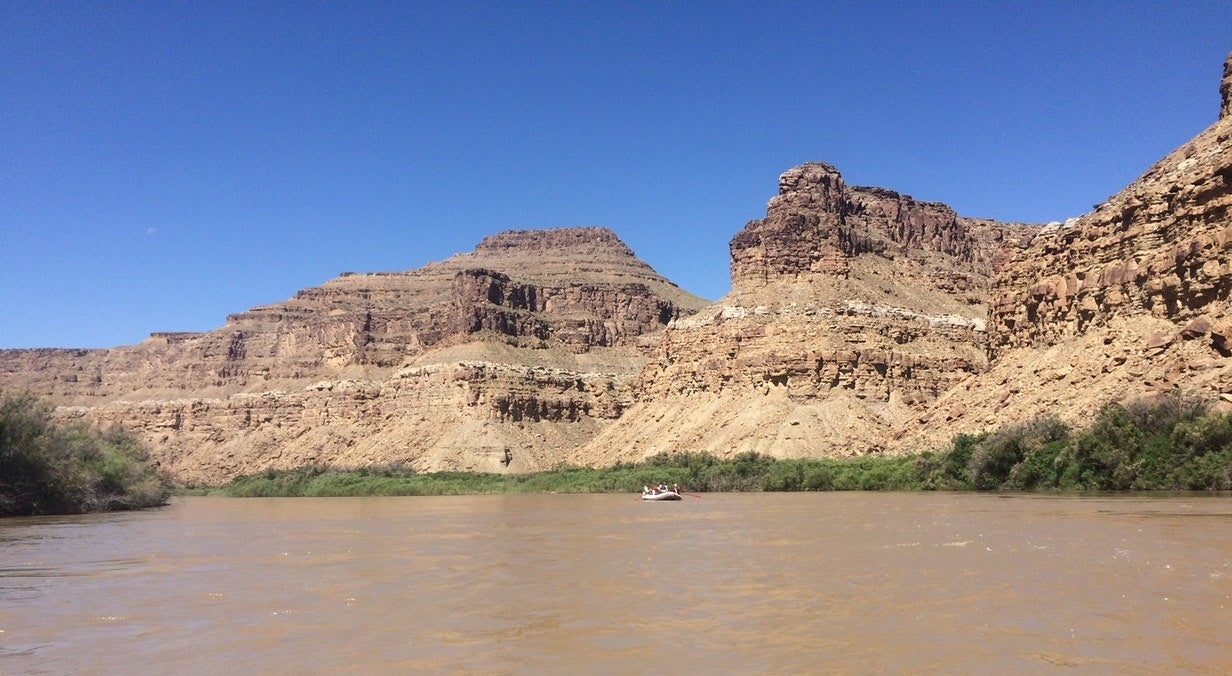 inflatable raft in the distance floats on muddy waters in utah desert