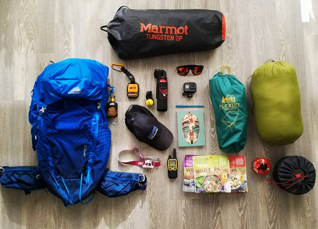 a backpacking pack, a tent, a chair and other smaller backpacking gear items laid out on a floor