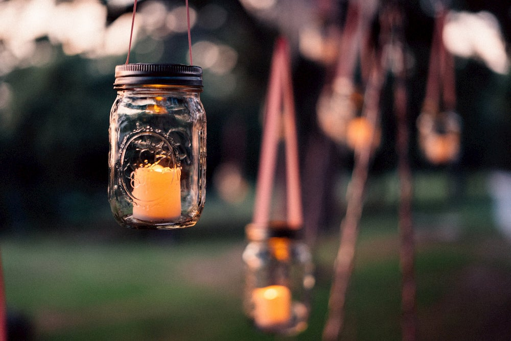 Mason jar with candle inside and blurry background