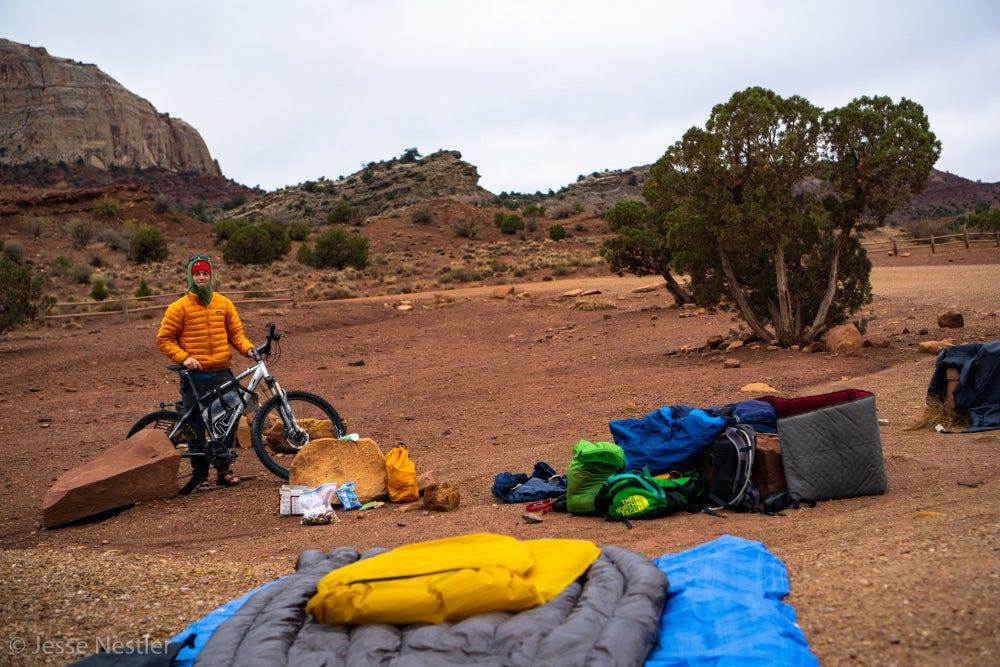 Man in yellow jacket holding mountain bike with sleeping bags in foreground