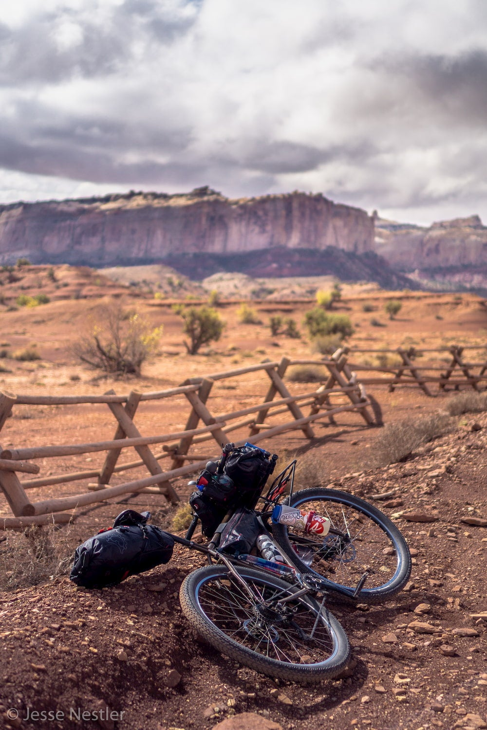 Bike laying on ground with fence and rock wall in background