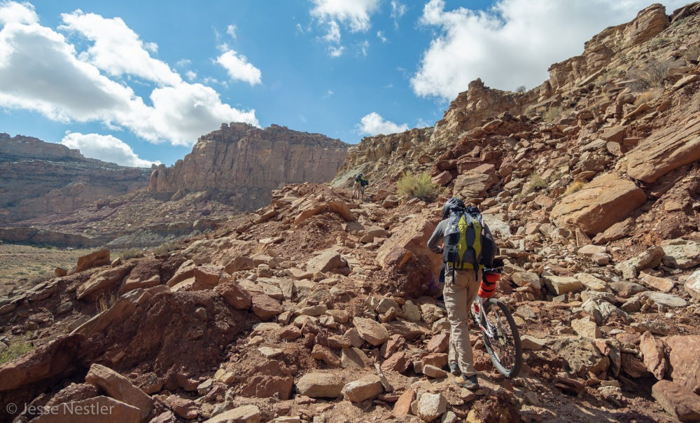 Man hiking up red rocks holding his mountain bike