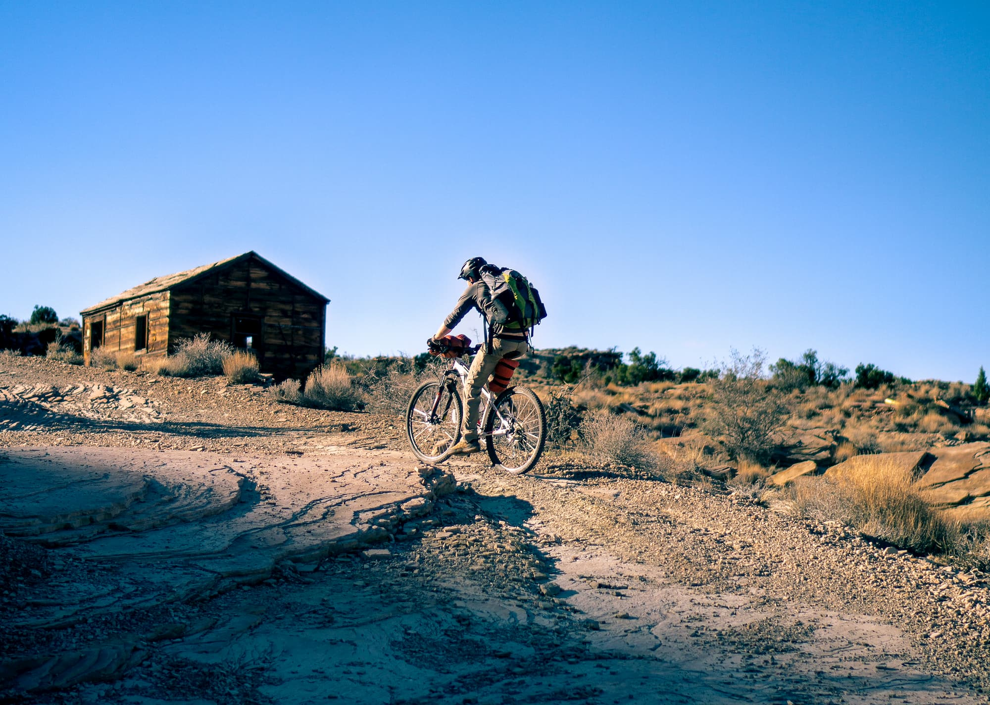Man riding bike along tail and shelter in background