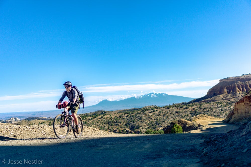 Man biking on trail with mountains and red rock in background