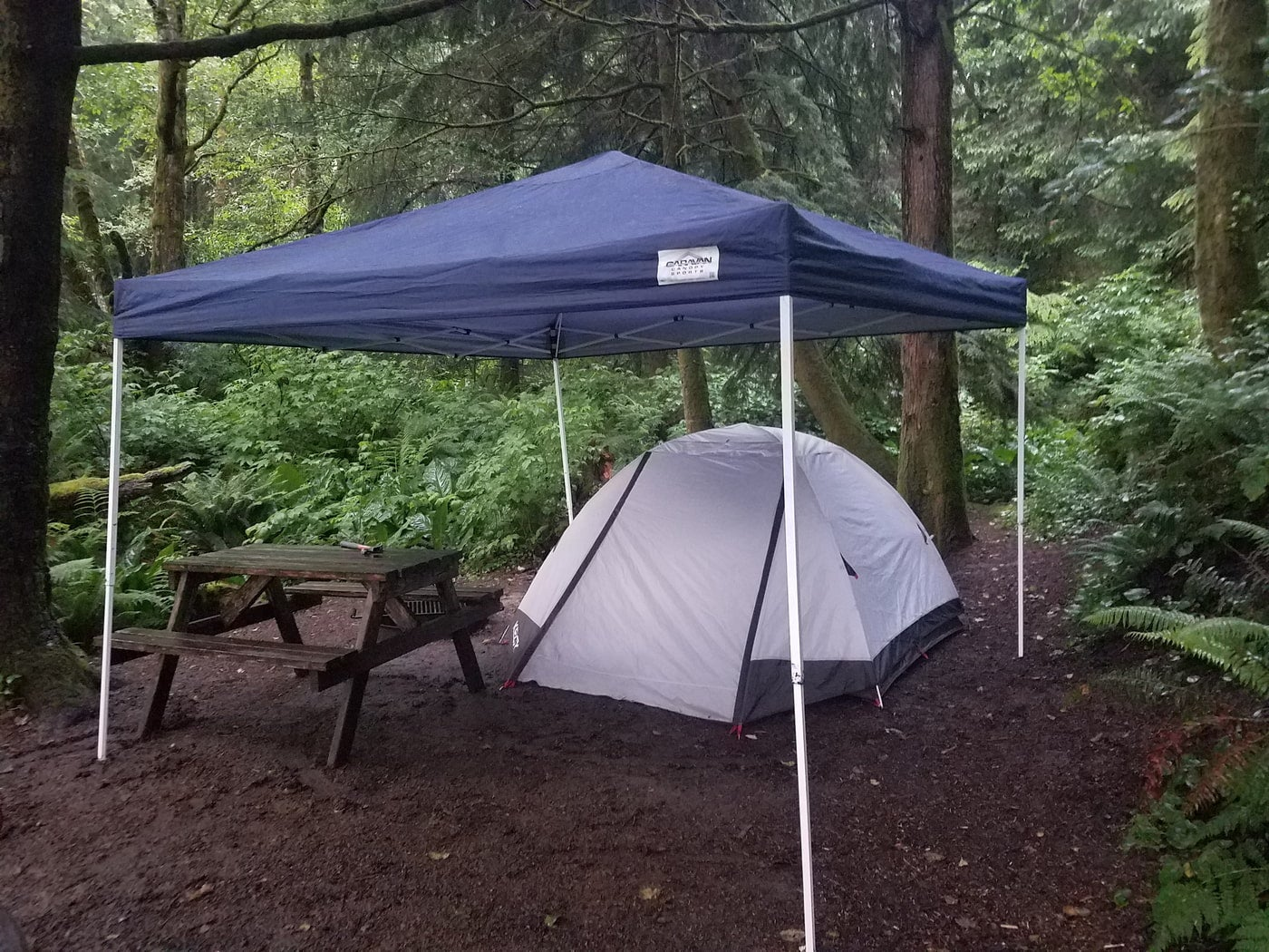 Tent under a canopy beside a picnic table at a forested campsite.