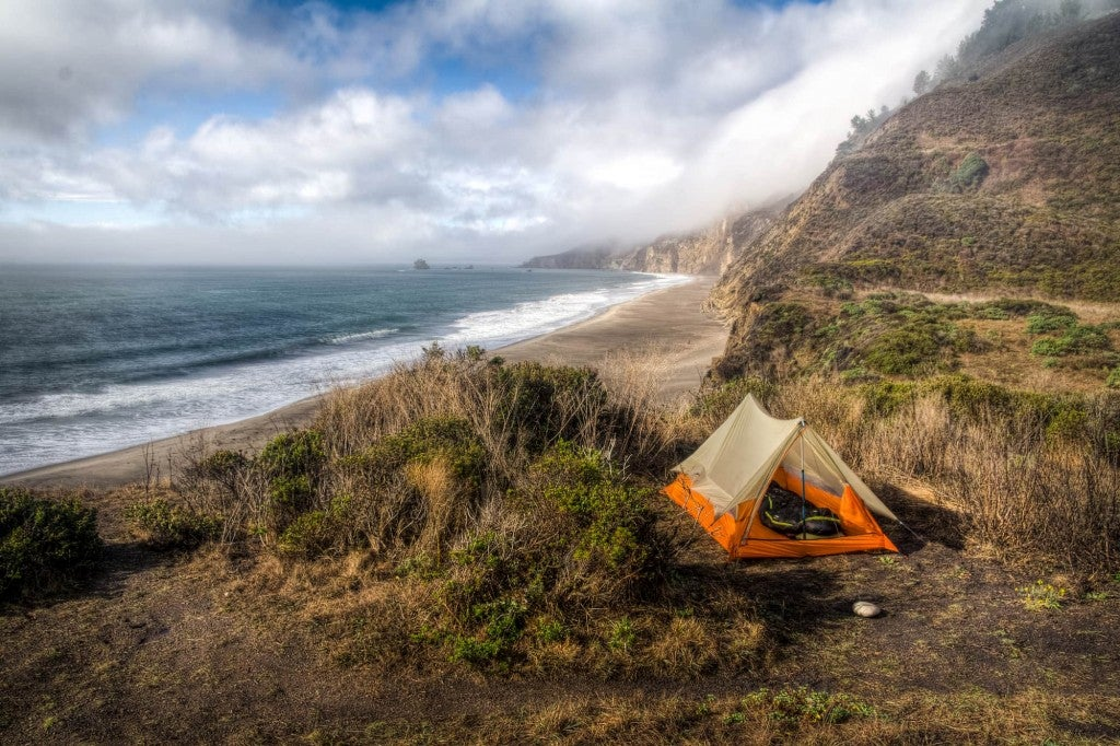 Orange tent set up in field above the north california coastline.