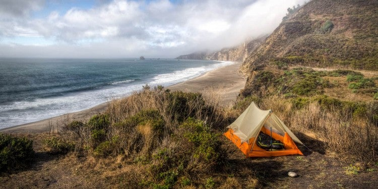 Orange tent set up in field above the north california coastline.