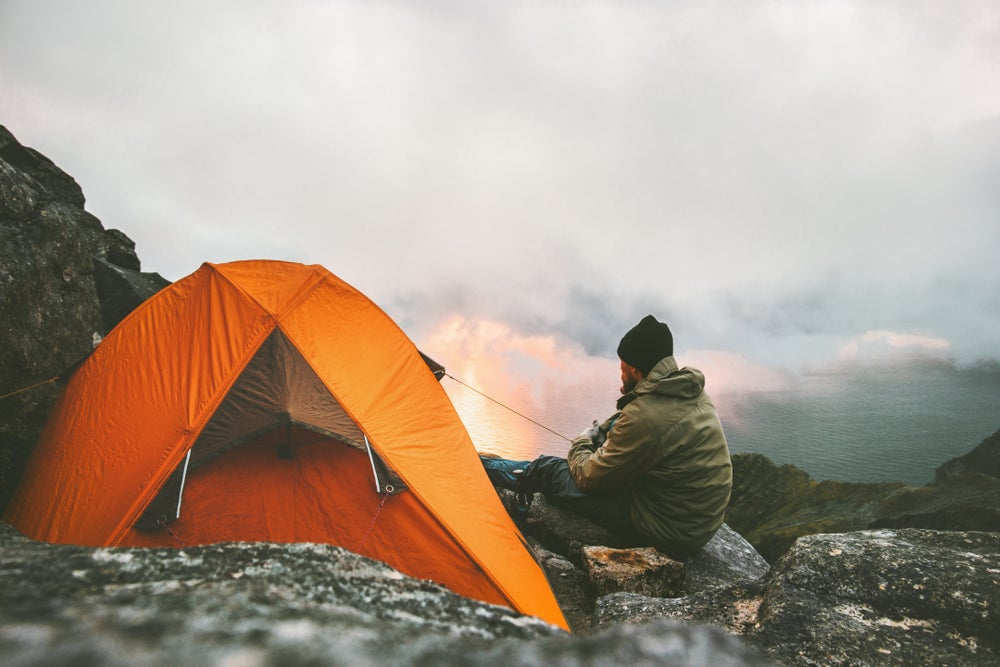 Man sitting on rocky mountainside beside an orange tent while looking out at the sunrise.
