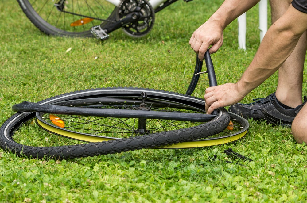 a person changing a bike's flat tire on a lawn.