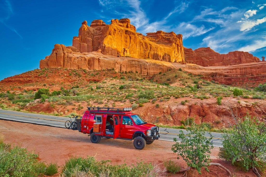 Red off roading adventure van with bikes on the back parked beside red rock formations of Arches Nation Park.