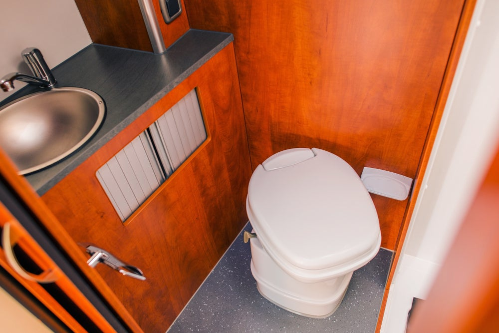 Cassette rv toilet in a wood lined rv bathroom.