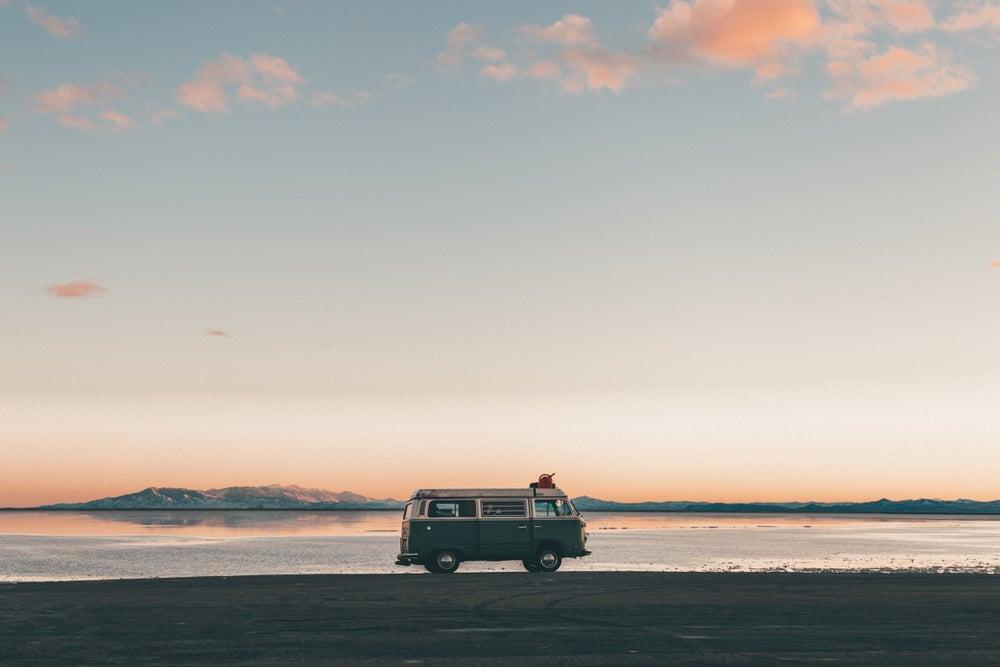 Old school VW van parked on the edge of Bonneville Sand Flats at sunset.