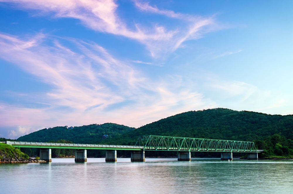 Panoramic view of rolling green hills with green bridge over river.