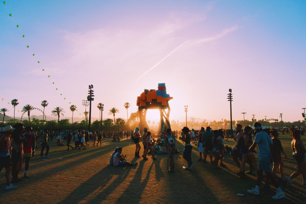 Art structure at music festival with palm trees and sunset in background